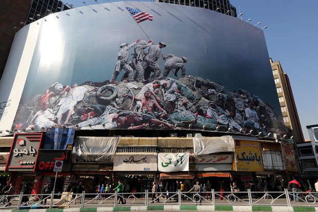 """A picture taken on January 18, 2016 shows an anti-US banner inspired by American photographer Joe Rosenthal's iconic World War II photograph """"Raising the Flag on Iwo Jima"""" displayed on a building in the capital Tehran. / AFP / ATTA KENARE"""