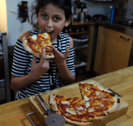 Iris cooks pizza in her kitchen in East Dulwich South London