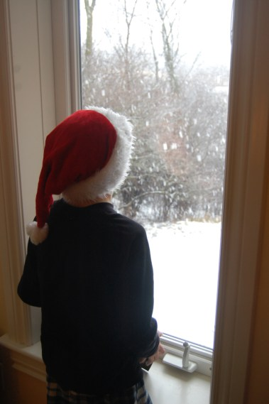 young-child-in-santa-hat-looking-out-at-snow-falling