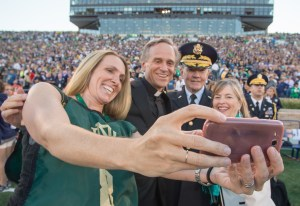 Chairman of the Joint Chiefs of Staff Gen. Martin E. Dempsey, his wife Deanie, Rev. John I. Jenkins, C.S.C., president of Notre Dame University, and a military spouse take a selfie on the field before a football game at Notre Dame Stadium in South Bend, Ind., Sept. 6, 2014. DoD Photo by Mass Communication Specialist 1st Class Daniel Hinton.