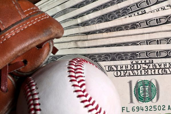 Baseball ball, glove and money on wooden table