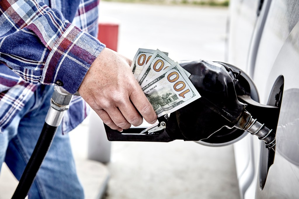 Man's hand holding three hundred US dollars and gas nozzle while  pumping gas into parked vehicle