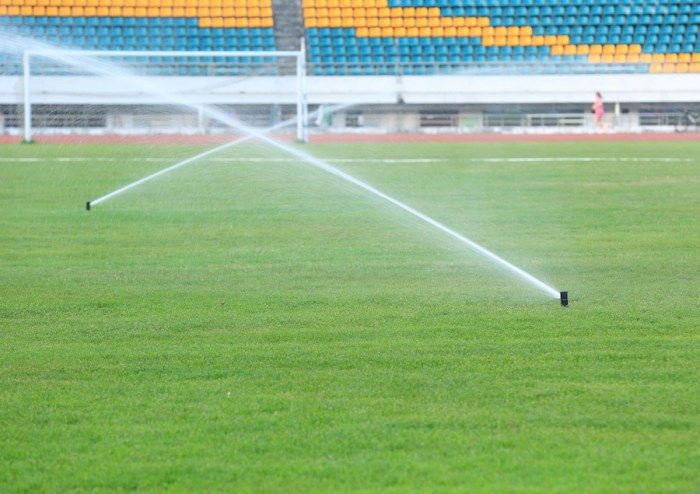watering green grass on football field