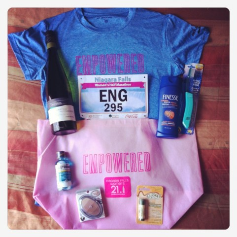 A pink race packet with a technical t-shirt, makeup, mouthwash, toothbrush and wine!