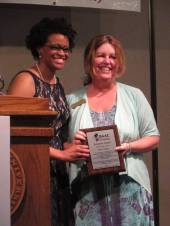 Dr. Charlae Davis presents WMU Catering banquet manager Megan McCoy with a Community Builder Award for sponsoring the ISAAC banquet.
