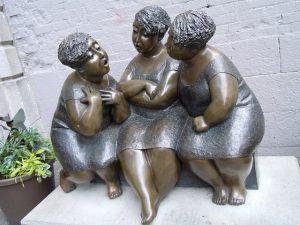 Statue intitulée Les Chuchoteuses où trois femmes sont en échange verbal et en totale attention