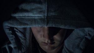 Un homme recouvert d'un épais manteau marche dans le noir