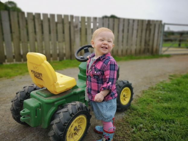 Our daughter with one of the rideable tractors at cefn mably farm