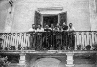 """Balcone di Palazzo Pierandrei, tra di loro Fangio, Marimon, p. Erasmo Percossi, Romeo Renzi, Pierino Pierandrei, """"Il Fachiro"""" e l'autista di Marimon.Fototeca Comunale """"B. Grandinetti""""."""