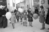 I bambini insieme alla suora Cappellona in via Mugellini. Fototeca Comunale Bruno Grandinetti.