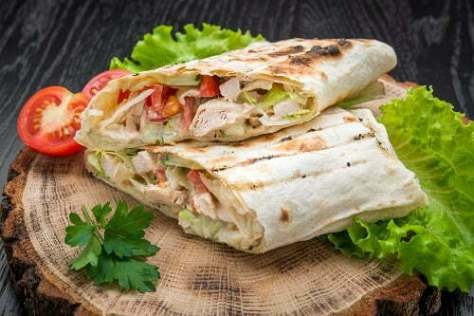 Tortilla wraps with grilled chicken or vegetarian tarteel of fresh vegetables on a wooden background.