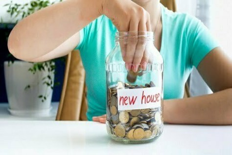 Closeup photo of young lady in blue T-shirt sitting at the white table on which is located ,full of coins , jar with the inscription new house