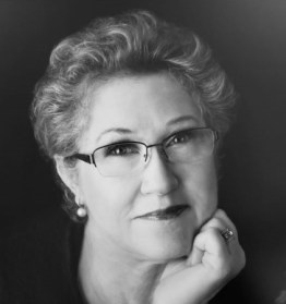 A black and white photograph of Catherine Van Son, who has short hair and is wearing glasses
