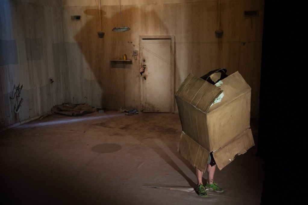 person in cardboard box in empty room