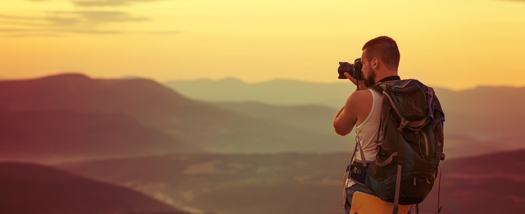 photographer looking over mountains into the sunset
