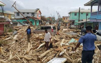 People walking through piles of wood from collapsed houses