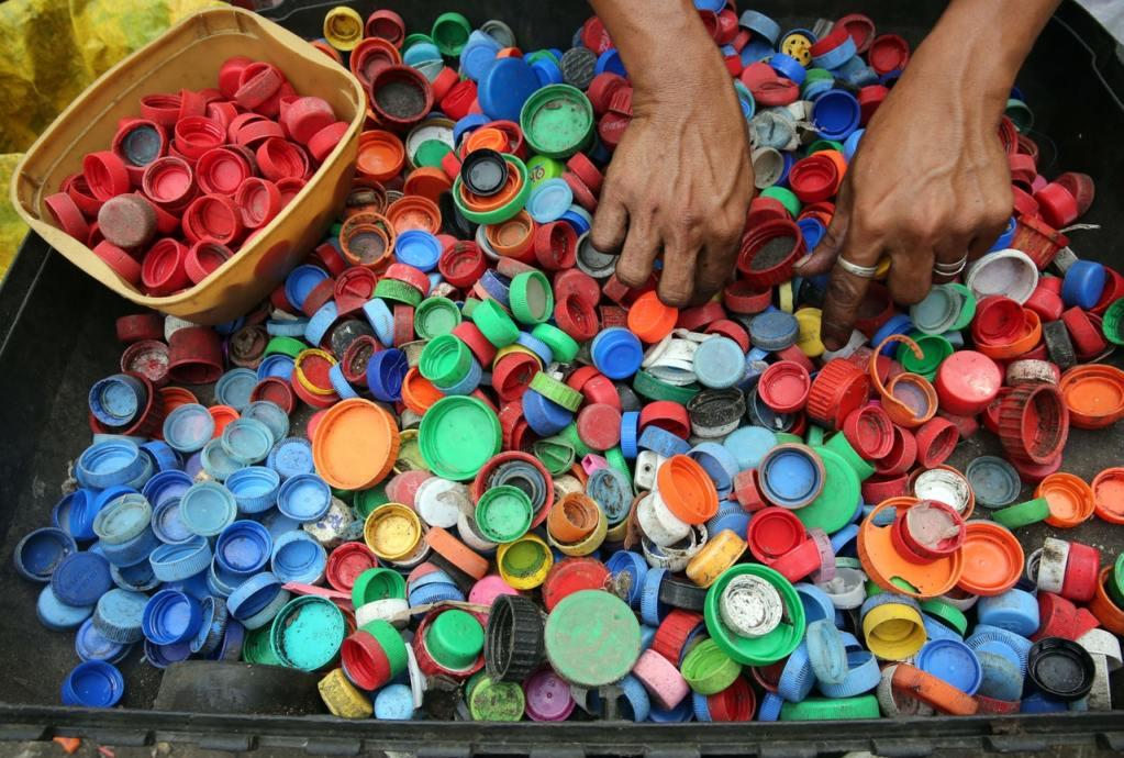 hands sorting plastic bottle caps