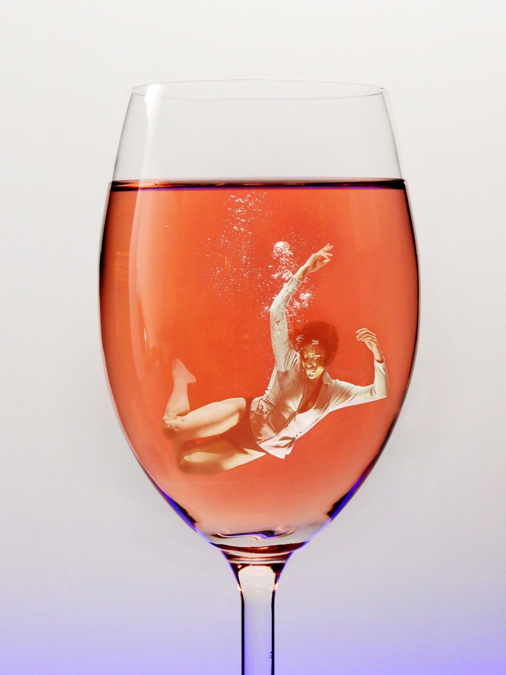 person swimming in a glass of alcohol