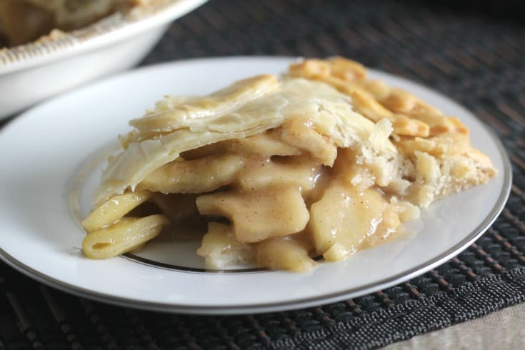 Close up view of apple pie on a white plate