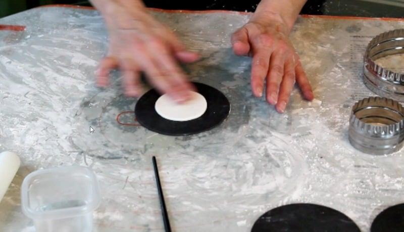 attaching white fondant circles for fidget spinner cake