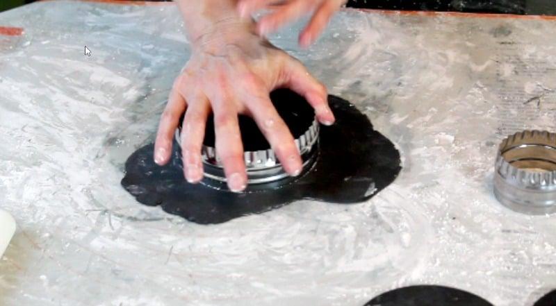 cutting black fondant circles for fidget spinner cake