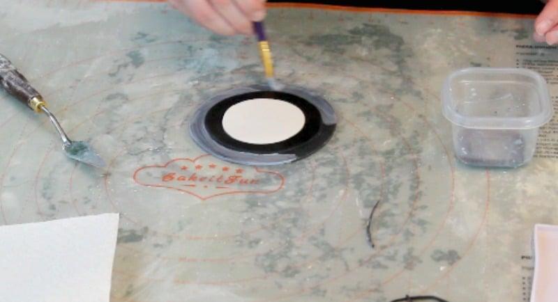 painting black fondant silver on the fidget spinner cake