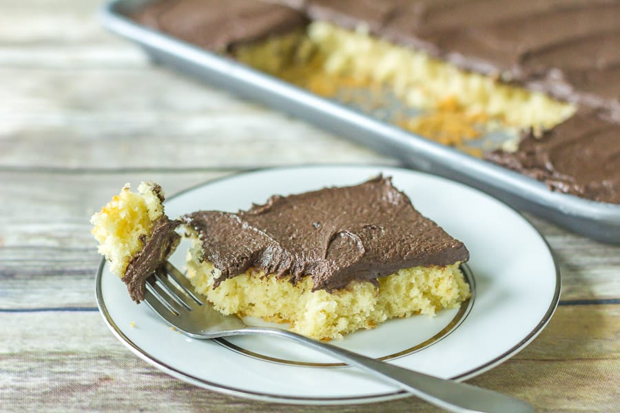 Yellow Buttermilk Sheet Cake with Fudge Frosting on a white plate with a fork