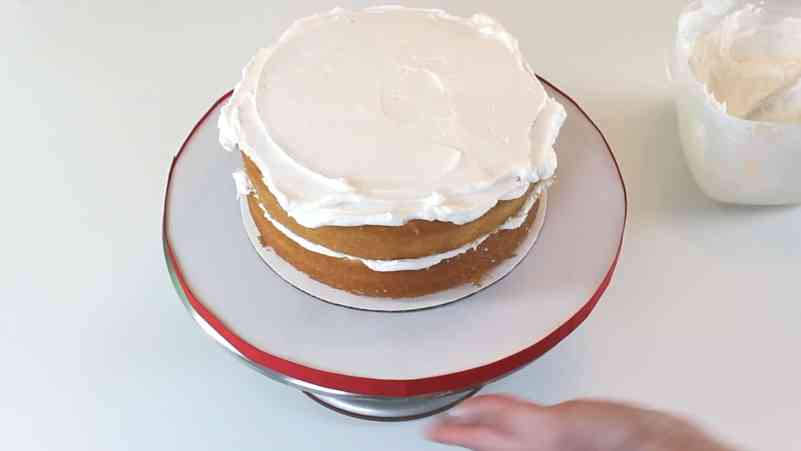 Smoothing buttercream layer on cake