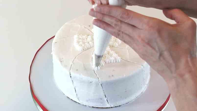 Piping white stars onto cake