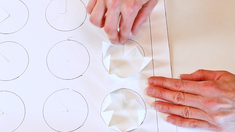 fold back cut outs in each circle of the cupcake box insert