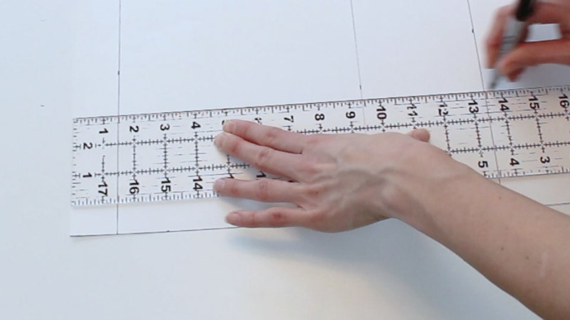 drawing a line to connect the measurements on the poster board