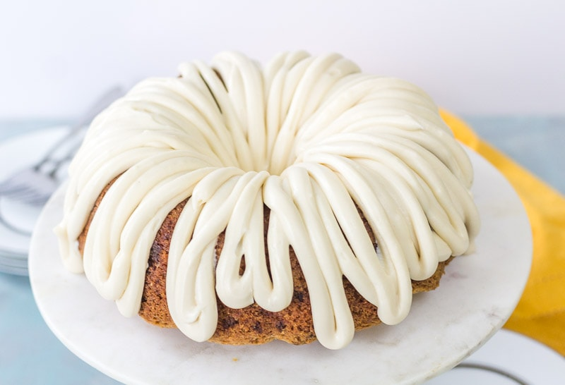 caramel carrot cake bundt cake with glace on a marble cake stand