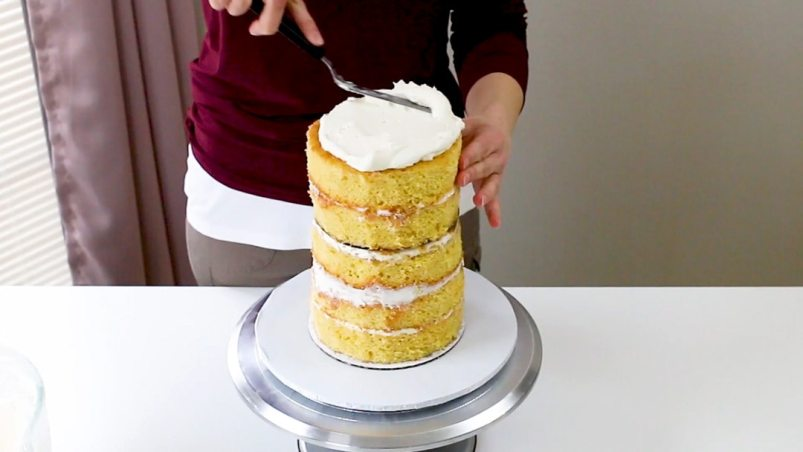 Add buttercream to the top of tall cake