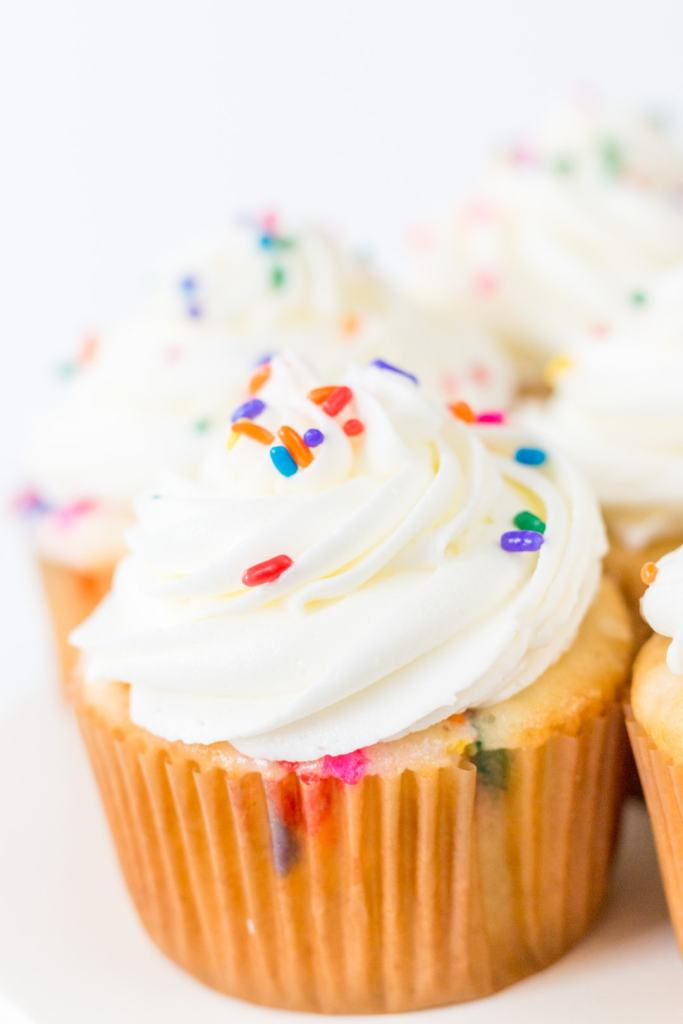 funfetti cupcakes close up with white icing and sprinkles