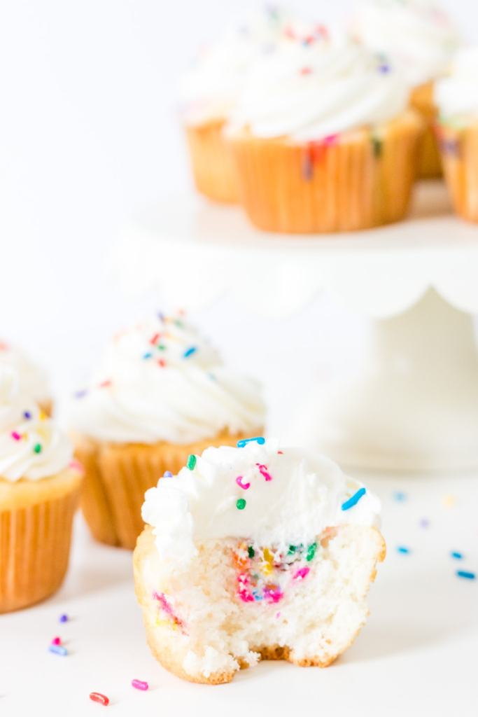 Funfetti Filled Cupcakes on a cake stand with sprinkles