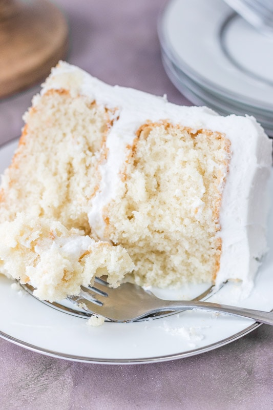 Slice of moist white cake on a white plate with a fork