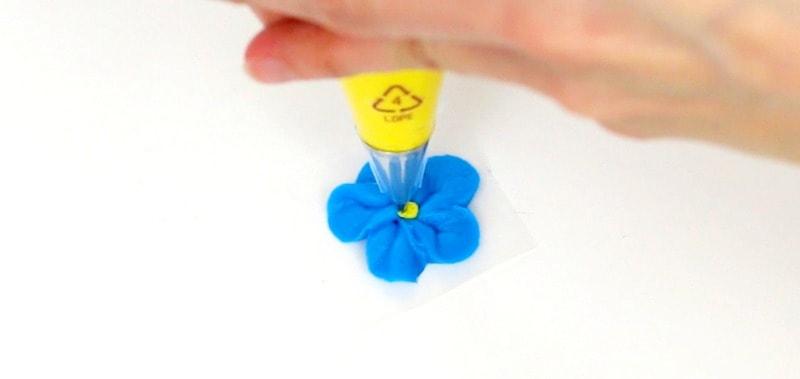 Blue buttercream flower with yellow center
