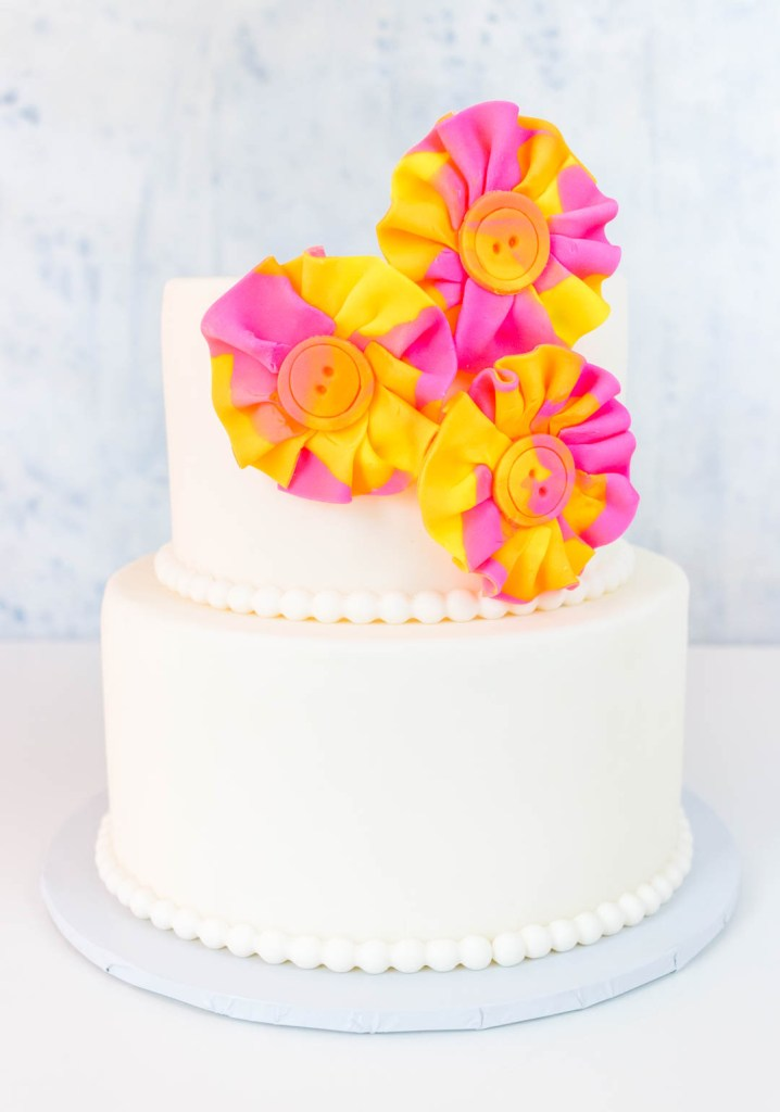 Two tiered white cake with watercolor fondant fabric look flowers