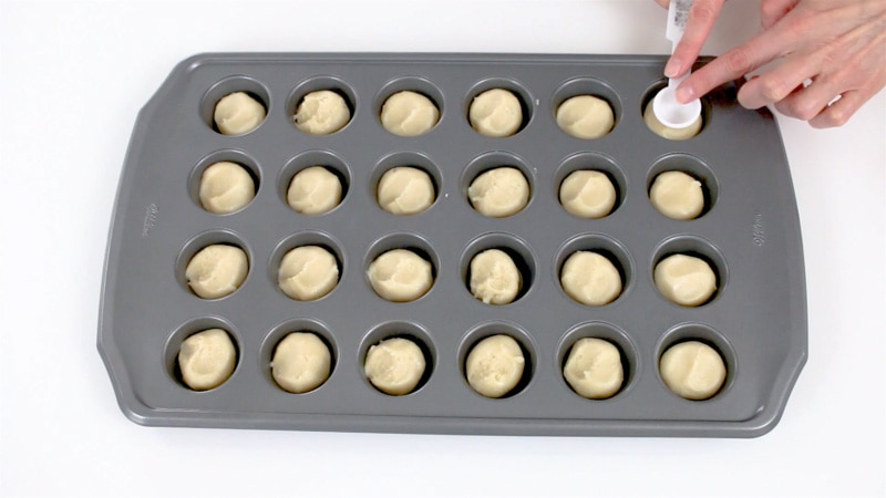 Pressing cookie dough into mini muffin pan to make cookie cups