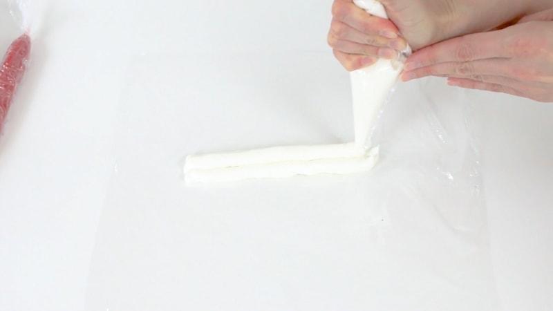 Adding white buttercream to saran wrap