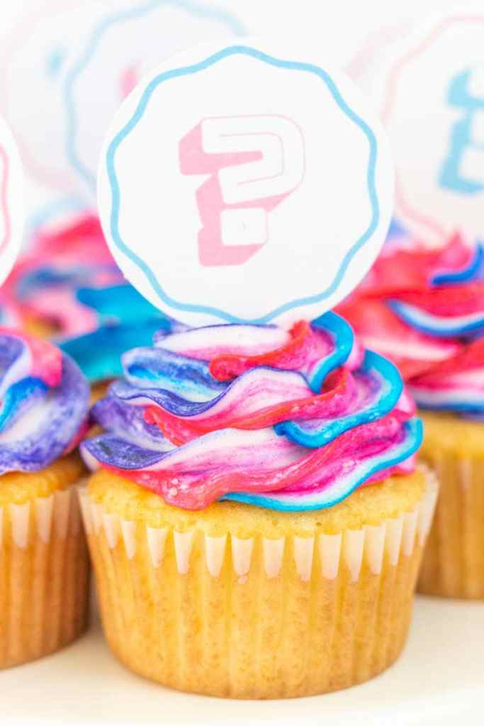 Gender reveal cupcakes with pastel cupcake toppers close up view