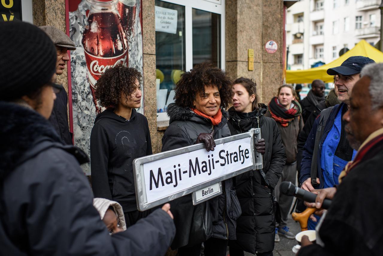 ISD, Dekoloniale, Jasmin Eding hält Straßenschild Maji-Maji-Str in der Hand umgeben von Leuten