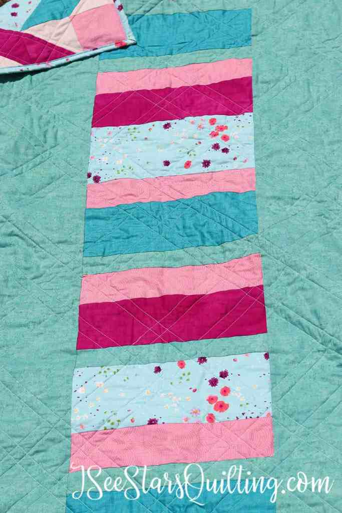 This is an example of a quilt back I created where instead of creating a normal seam of 2 same fabrics together, I added a column of striped fabric to the back of my quilt for added interest.