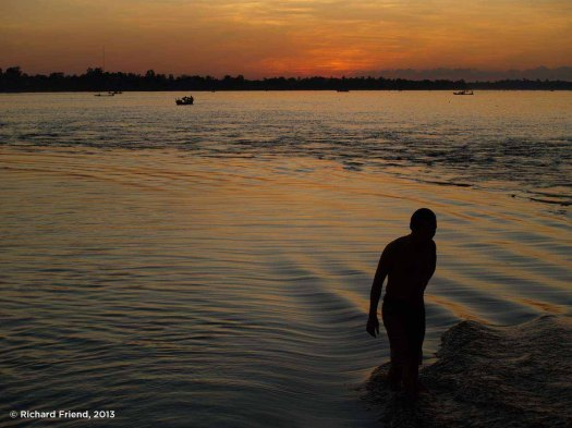 As the sun sets on the Mekong river in Northern Cambodia, local people take an evening bath