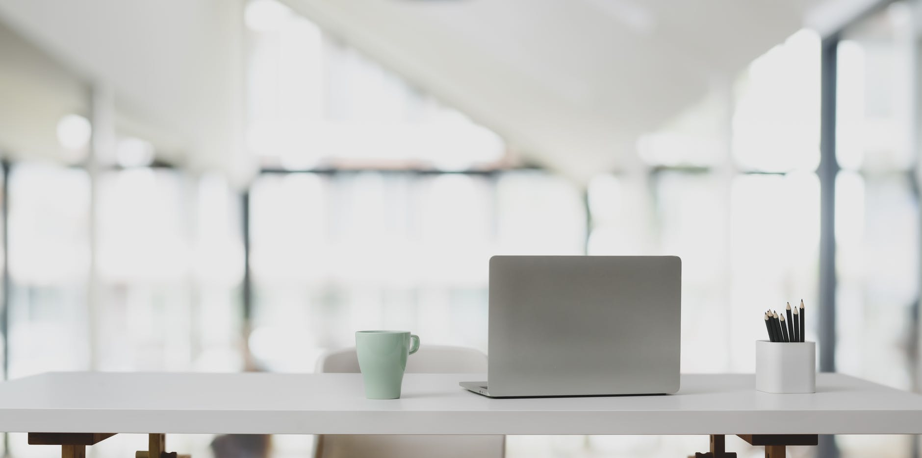silver laptop in white wooden table