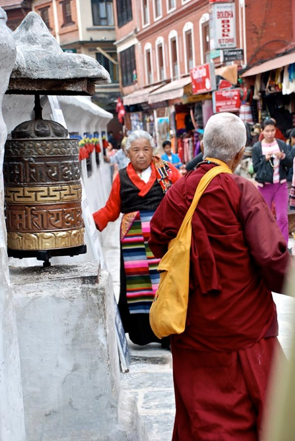 A Buddhist practitioner walks past a line of prayer wheels spinning them while chanting Mantras