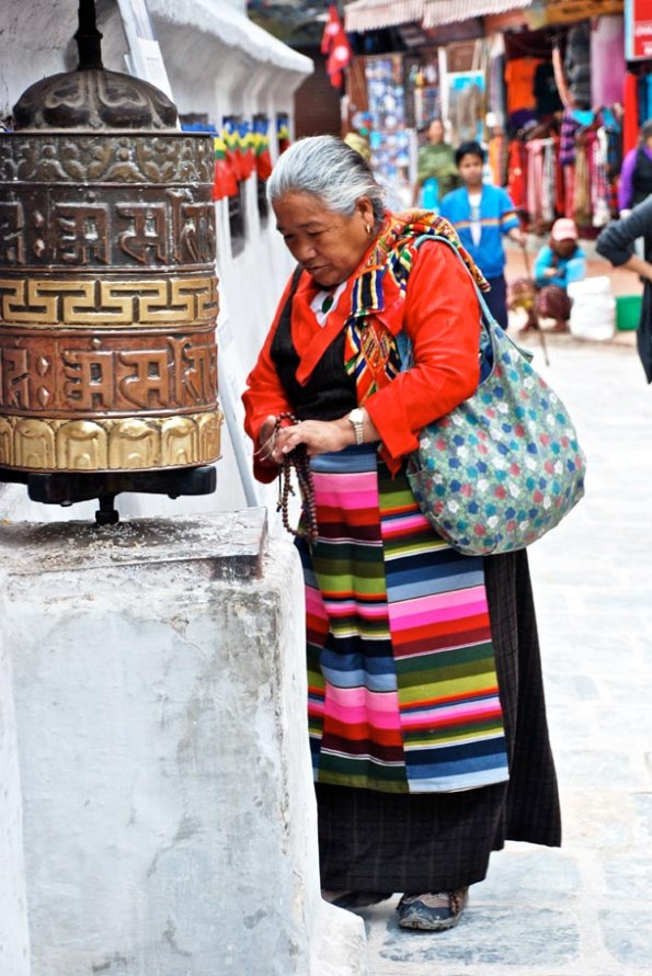 A Buddhist practitioner spins the prayer wheel, re-inforces her prayers with prayer beads