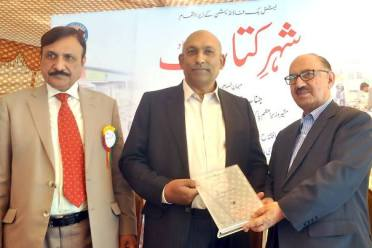 CEO Kitab Ghar Khalid Masood offering shield to Irfan Siddiqui at the inauguration of 'Shehr-e-Kitab'. Managing Director NBF Dr Inamul Haq is also seen