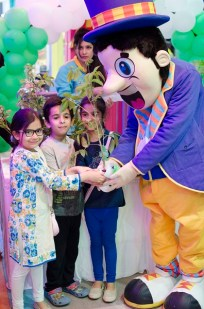 Fun City mascot giving away plant sapling to the kids on Earth Day 2016