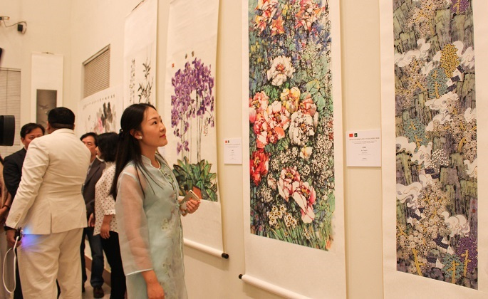 A visitor looks at the paintings by Chinese artist Ke Tongzhi at art exhibition by Pakistani and Chinese artists at PNCA in Islamabad on 18 Oct. 2016.